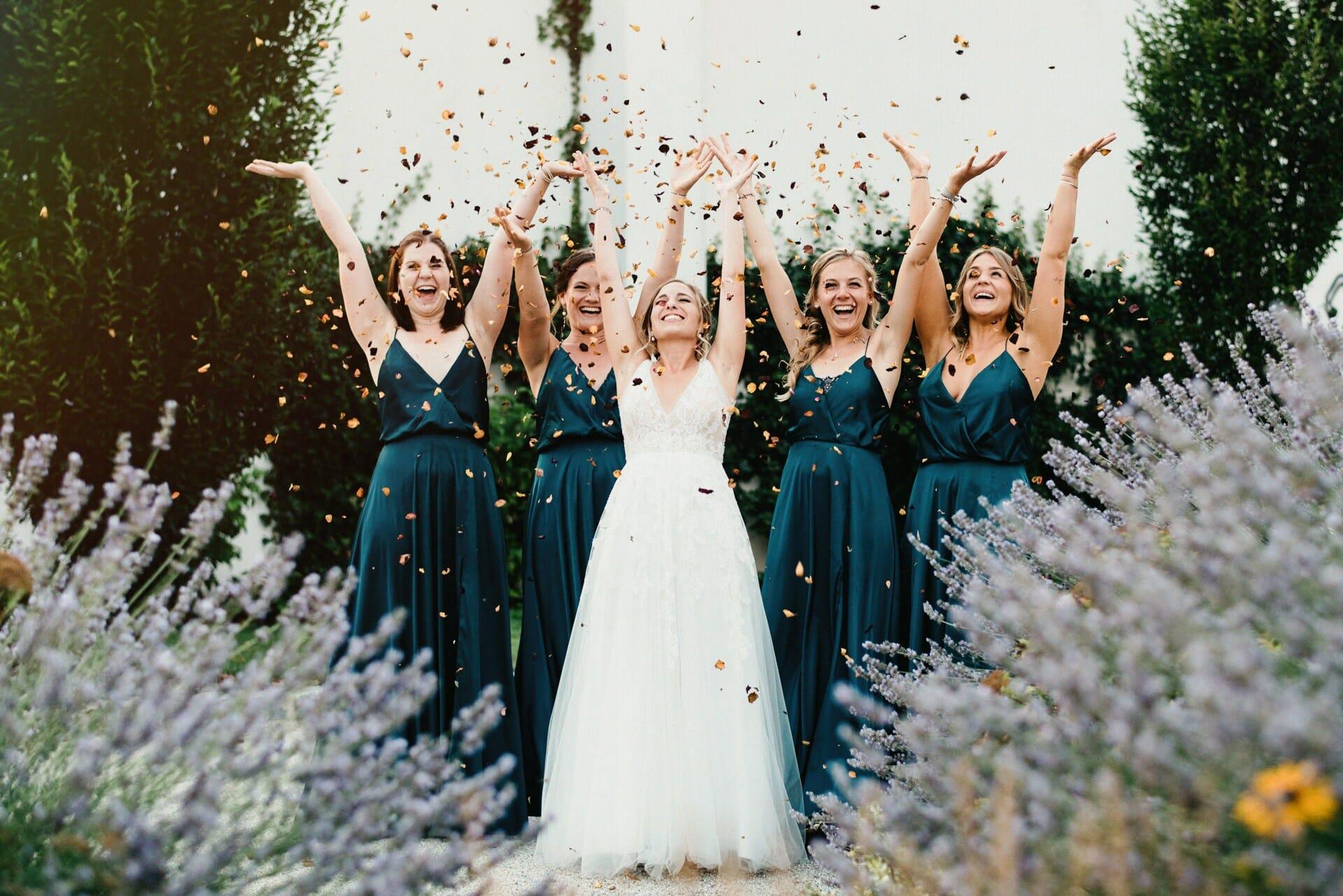 Braut mit ihren Brautjungfern wirft Blüten in die Luft und alle haben eine Freude